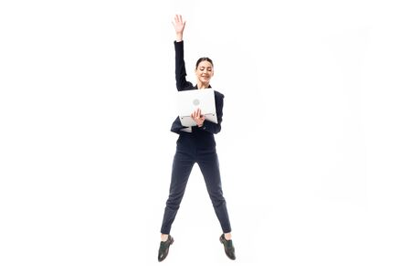 attractive businesswoman jumping while holding laptop isolated on white Foto de archivo