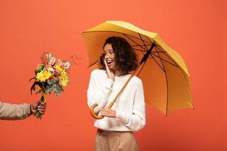 boyfriend gifting shocked woman with umbrella bouquet of flowers isolated on orange 版權商用圖片