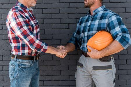 cropped view of men shaking hands while standing near brick wall