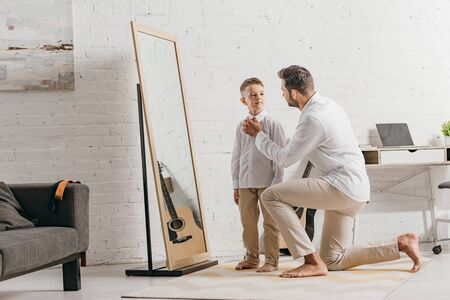 father helping son to get dressed near mirror