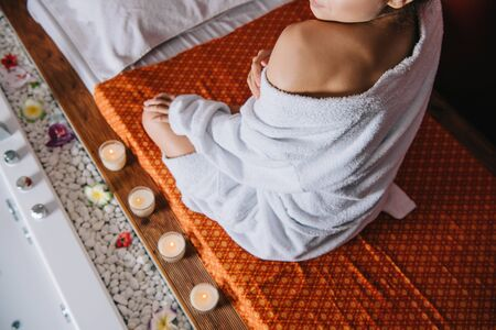 cropped view of woman in bathrobe sitting on massage mat in spa salon