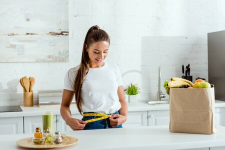 happy young woman measuring waist near groceries