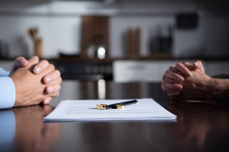 partial view of couple sitting at table with clenched hands near divorce documents Stockfoto