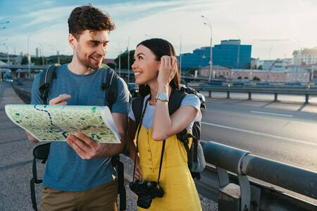 handsome man holding map and looking at asian woman in overalls