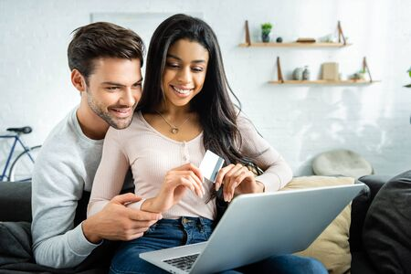 smiling african american woman holding credit card and looking at laptop with man Banco de Imagens