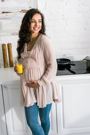cheerful pregnant woman holding glass with fresh orange juice