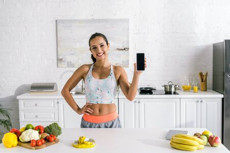 cheerful woman holding smartphone with blank screen and standing with hand on hip