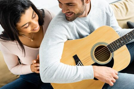 smiling african american woman looking at man with acoustic guitar Banco de Imagens
