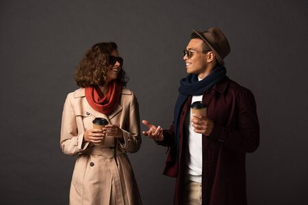 smiling stylish interracial couple in autumn outfit with coffee to go talking on black background