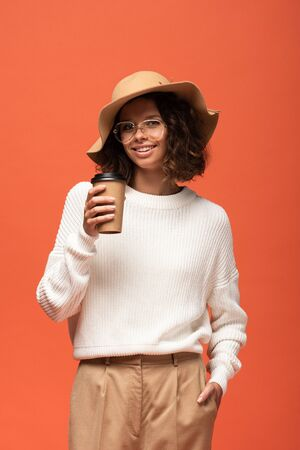 smiling woman in hat and glasses holding coffee to go isolated on orange Stock Photo