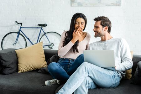 smiling african american woman sitting on sofa and handsome man holding laptop