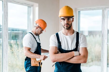 selective focus of handsome handyman in goggles standing with crossed arms near coworker