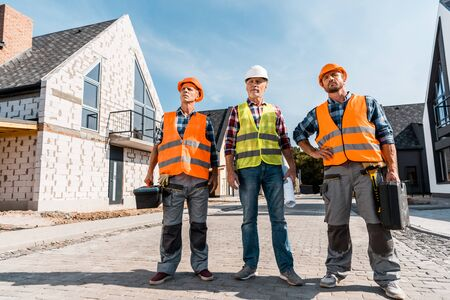 middle aged constructors in helmets standing with coworker near houses