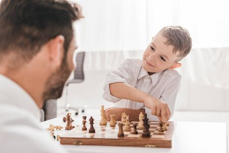 selective focus of dad and son playing chess together at home