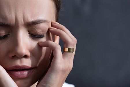 partial view of upset young woman with ring with closed eyes