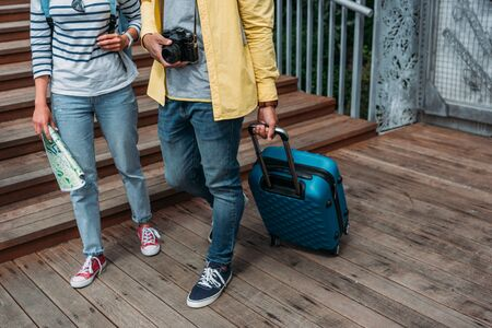 cropped view of multicultural woman and man walking with blue luggage