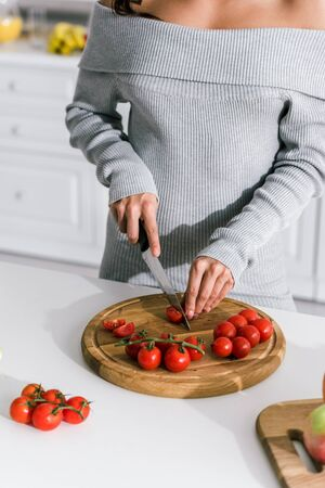 cropped view of girl holding knife near cherry tomatoes