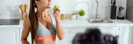 panoramic shot of happy woman smelling tasty apple