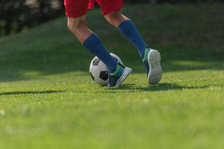 cropped view of kid in sportswear running on green grass with football 写真素材
