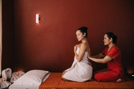 asian masseur wrapping with towel attractive woman in spa salon Stock Photo