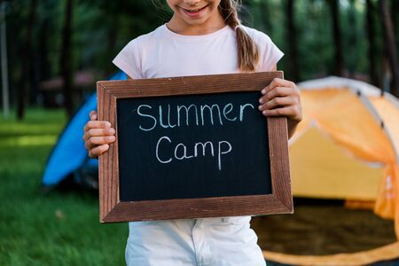 cropped view of happy kid holding chalk board with summer camp letters