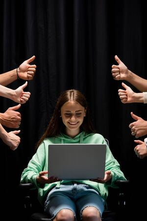 partial view of people showing thumbs up and smiling girl holding laptop on black