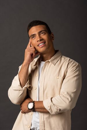 dreamy handsome mixed race man in beige shirt on black background