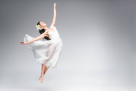 graceful ballerina in white dress jumping while dancing on grey background