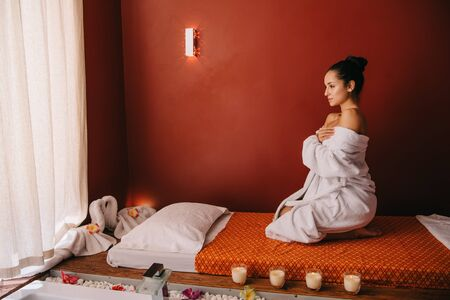 attractive woman in bathrobe sitting on massage mat in spa salon