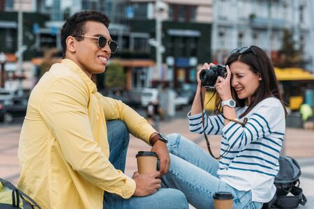 Woman sitting and taking photo of multiracial man in sunglasses and coffee cup Фото со стока