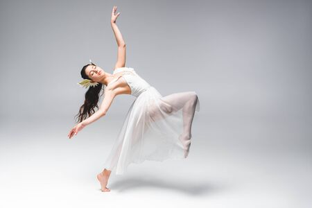 beautiful young ballerina in white dress dancing on grey background