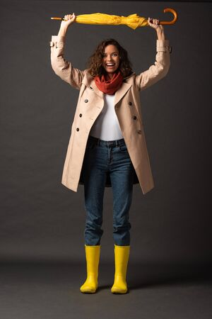 happy woman in trench coat and rubber boots holding yellow umbrella above head on black background Stock Photo