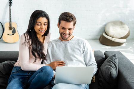 smiling african american woman and handsome man looking at laptop