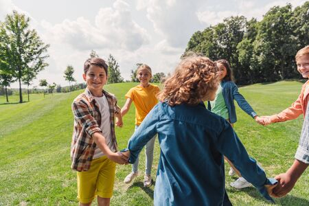 selective focus of happy multicultural kids holding hands in park Stock Photo