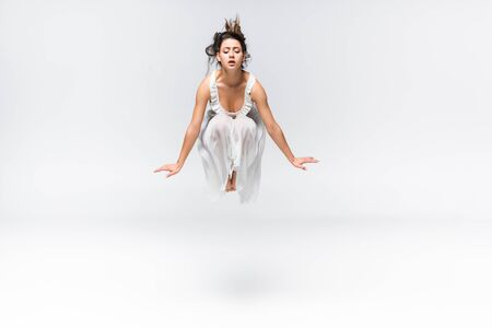 beautiful young ballerina jumping in dance on grey background