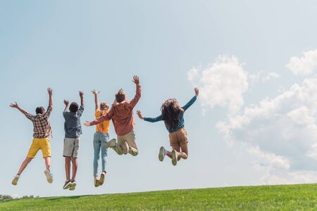 back view of multicultural kids jumping and gesturing against blue sky Фото со стока