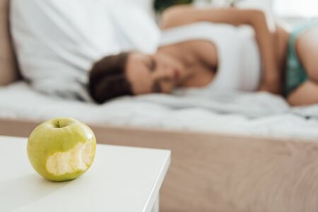 selective focus of suffering woman touching belly and green apple on foreground