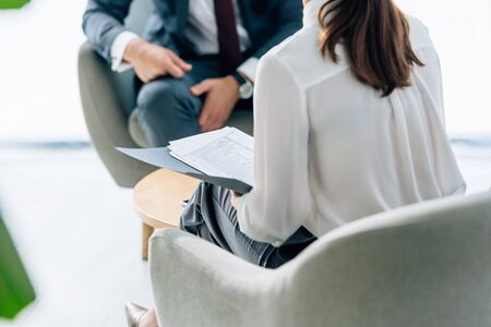 cropped view of businessman in suit talking with journalist