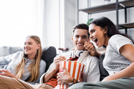 multicultural friends sitting on sofa and eating popcorn in apartment Фото со стока