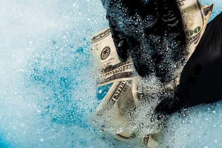close up of man in rubber gloves washing dollar banknotes in soap bubbles with water