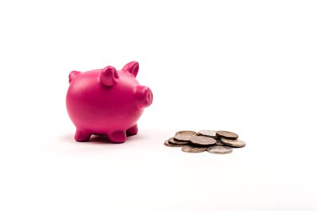pink piggy bank near silver and golden coins on white