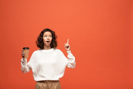 excited woman holding coffee to go and showing idea gesture isolated on orange