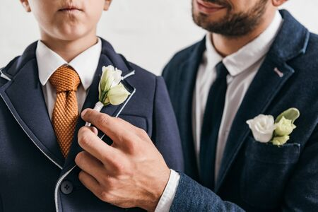 partial view of son and dad in jackets with boutonnieres