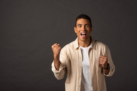 excited handsome mixed race man in beige shirt showing yes gesture on black background 스톡 콘텐츠