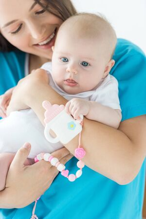 attractive and smiling mother holding her child with toy in hospital