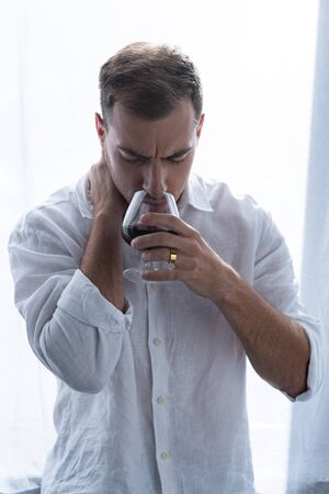 front view of depressed man in shirt drinking cognac at home