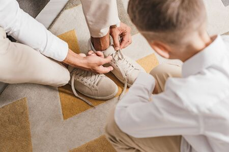 partial view of father teaching son to tying shoelaces at home 写真素材