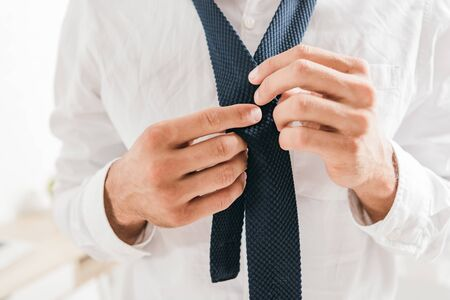partial view of man in white shirt tying tie