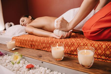 cropped view of masseur doing massage with herbal ball to woman in spa