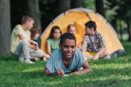 selective focus of happy african american boy holding pencil near notebook and friends in camp